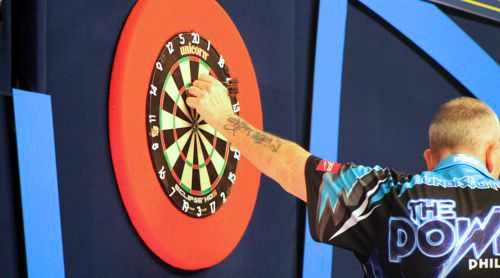 Phil Taylor zieht die Darts aus dem Dartboard